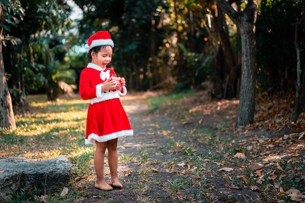 赤いサンタクロースの衣装を着た小さなアジアの女の子は、公園のプレゼントボックスで驚きを感じます