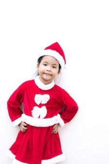 Маленькая азиатская девушка в красном костюме санта-клауса на белом фоне
