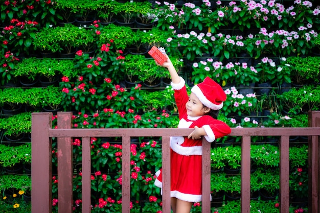 Маленькая азиатская девушка в красном костюме санта-клауса с настоящей коробкой в парке
