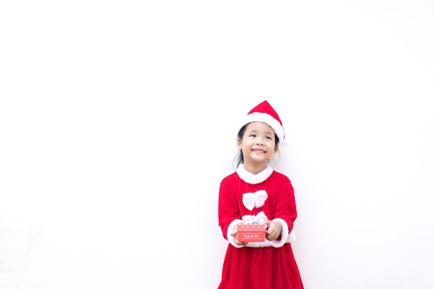 Маленькая азиатская девушка в красном костюме санта-клауса с подарочной коробкой на белом фоне