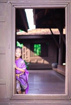 古代の家に立っているタイの時代のドレスの小さなアジアの女の子