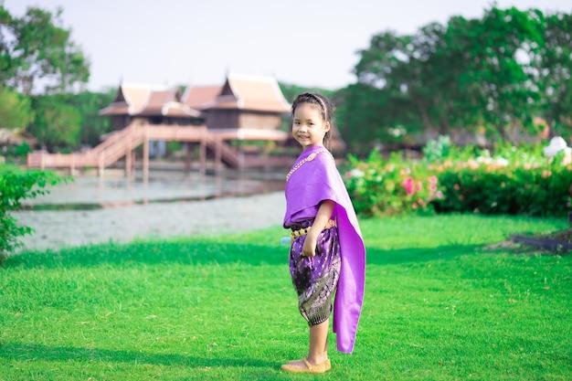 公園に立っているタイの時代のドレスの小さなアジアの女の子