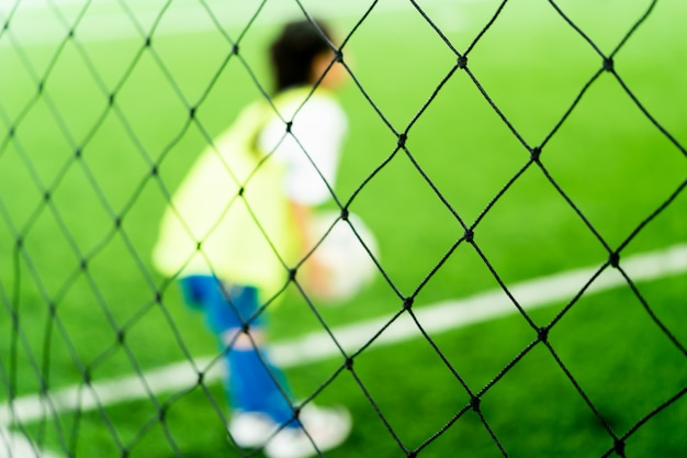小さなアジアの女の子が屋内のサッカー場で練習しているぼやけた
