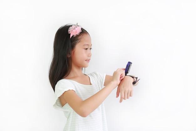 白い背景に対してスマートウォッチビデオカメラを使用して小さなアジアの女の子の子供