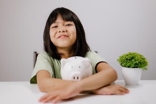 小さなアジアの女の子は貯金箱が大好きです。笑顔でお金を節約して幸せ