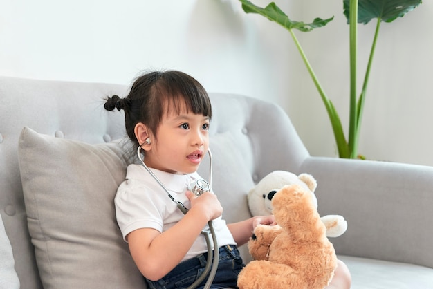 Little asian girl play with baby doll toy