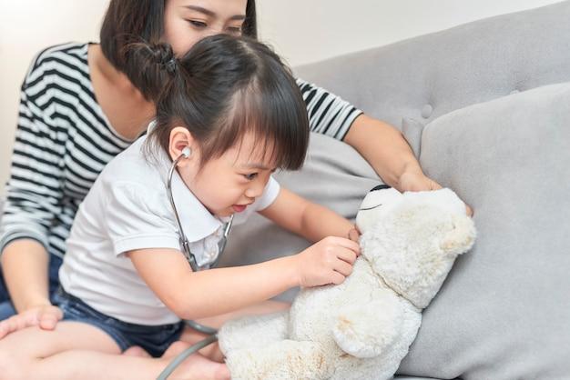 小さなアジアの女の子が赤ちゃん人形のおもちゃで遊ぶ