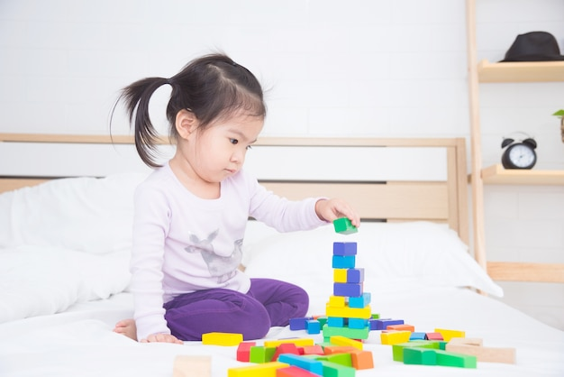 Little asian girl playing colorful wooden blocks on bed