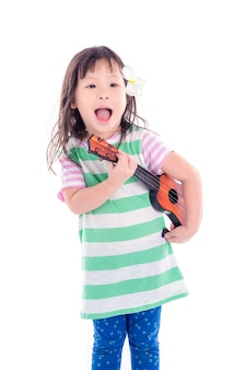 Little asian girl playing guitar toy over white background