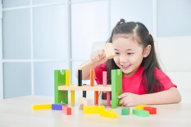家でおもちゃを遊んでいる小さなアジアの女の子