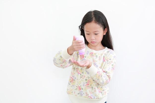 白い背景の上に手にタルカムパウダーを注ぐ小さなアジアの女の子
