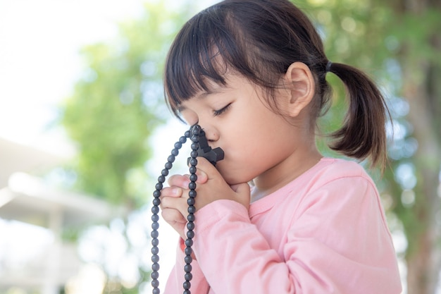 Little asian girl praying with holding the cross, christian concept.