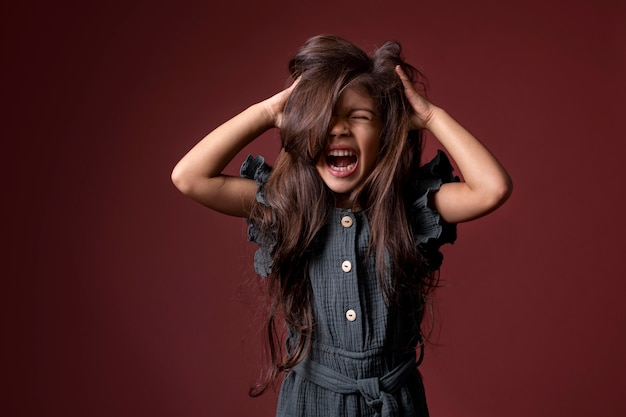 彼女の髪に彼女の手を叫んで持っている小さなアジアの女の子