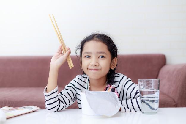 Маленькая азиатская девушка сидя на белом столе к еде лапши быстрого приготовления