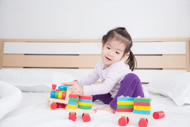 Little asian girl sitting on bed and playing toys at home
