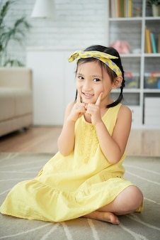 Little asian girl sitting on floor at home and posing with fingers on cheeks