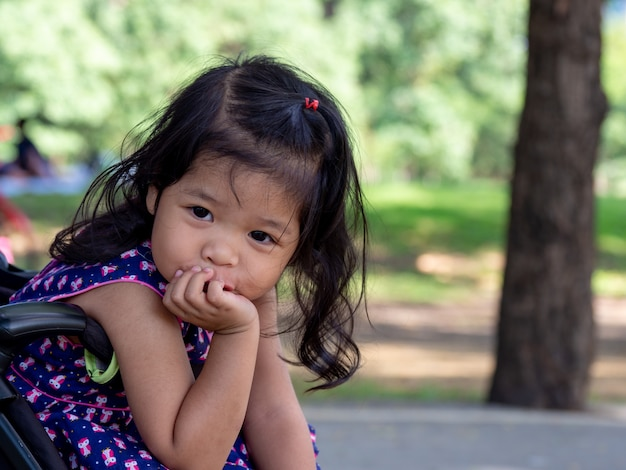 Little asian girl sitting in a stroller at public park. she have be smile