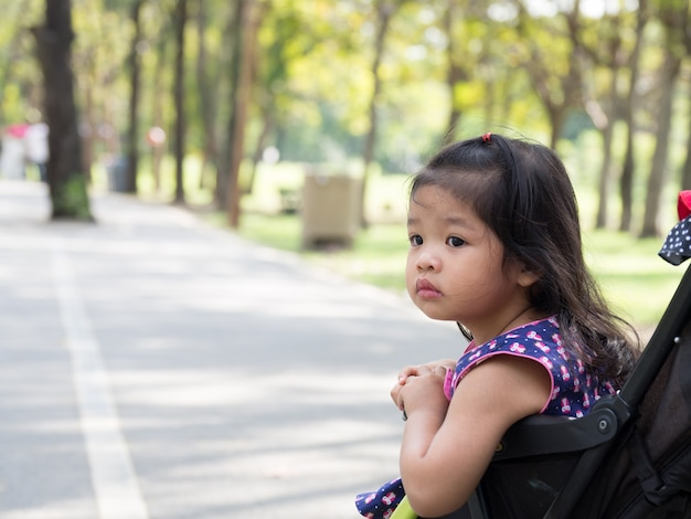Little asian girl sitting in a stroller at public park.