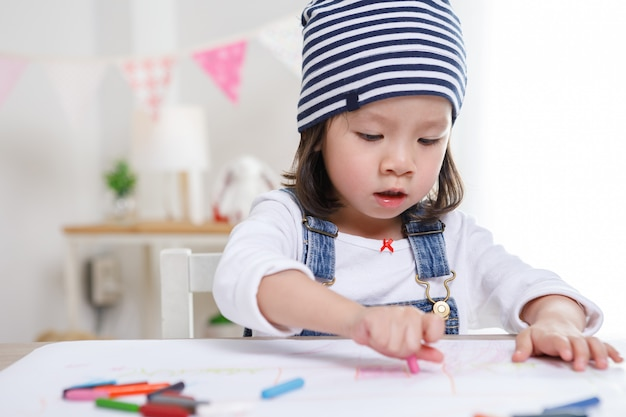 Little asian girl sitting at table in room, preschooler girl drawing on paper with colorful pens on sunny day, kindergarten or