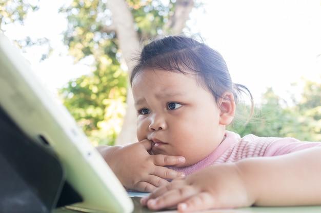 デジタルタブレットを見ながら座っているアジアの少女。現代の子供たちのために学んでいますが、子供たちの目や反射神経に悪影響を与える可能性があります。