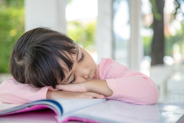 Маленькая азиатская девочка спит на столе в классе