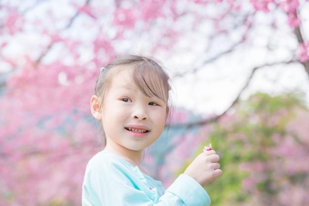 Маленькая азиатская девушка усмехаясь перед деревом сакуры.