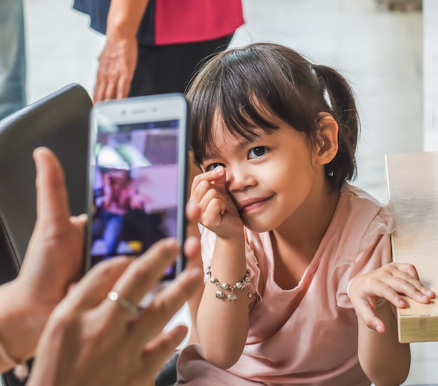 Little asian girl take a photo with a smartphone.