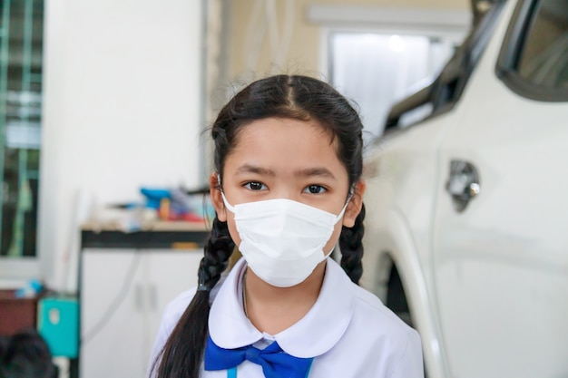 Little asian girl in thai student uniform wearing virus protective flu mask, health care concept, select focus shallow depth of field