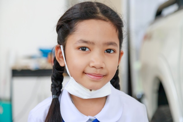 Little asian girl in thai student uniform wearing virus protective flu mask