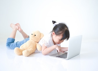 Little Asian girl typing message on laptop over white background.