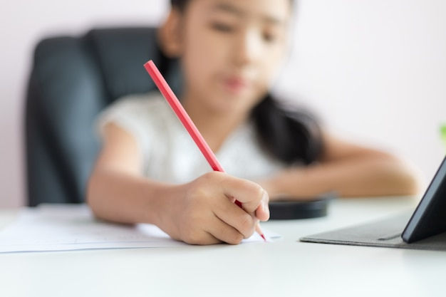 Little asian girl using the pencil to write on the paper doing homework for education concept