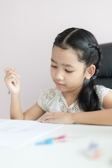 Little asian girl using the pencil to write on the paper doing homework and smile