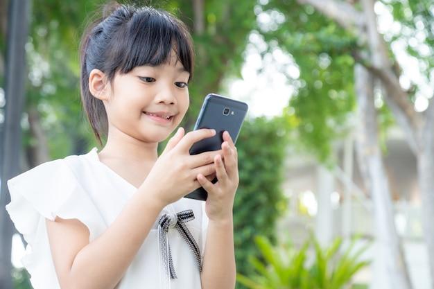 カフェでスマートフォンを使用している小さなアジアの女の子。自然光のアウトドアライフスタイル。