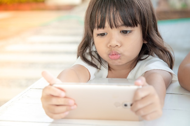 Little asian girl using smart phone at cafe. natural light outdoor lifestyle.