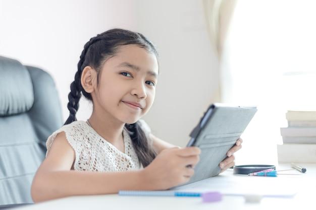 タブレットを使用して小さなアジアの女の子と教育概念の幸福と笑顔