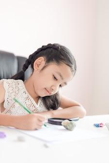 鉛筆を使用して、教育の概念のための宿題をしている紙に書く小さなアジアの女の子