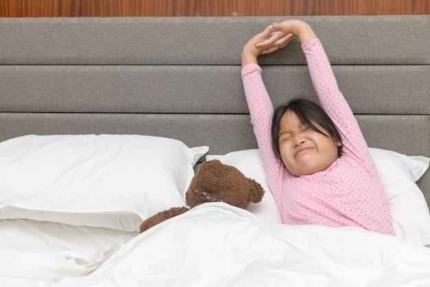 Маленькая азиатская девушка просыпается и растягивается на кровати утром, концепция мира здравоохранения и доброго утра
