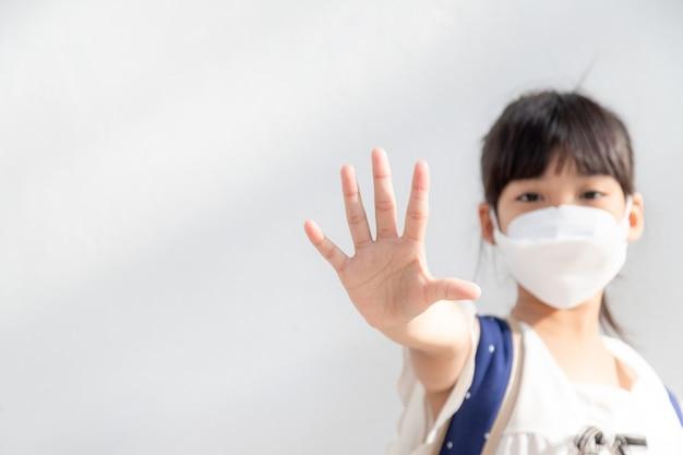 保護のためのマスクを身に着けている小さなアジアの女の子は、コロナウイルスの発生を止めるために手のジェスチャーを停止します