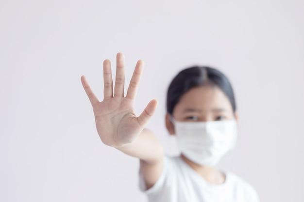 保護のための医療用マスクを着用し、武漢コロナウイルスの集団発生を阻止するためのストップジェスチャーを示すアジアの少女。