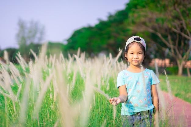 公園の草の花とキャップを着ている小さなアジアの女の子