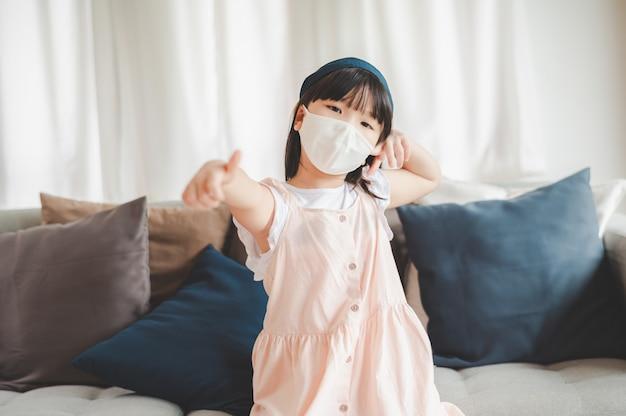 コロナウイルスからの保護のためにフェイスマスクを身に着けている小さなアジアの女の子は、家で親指を表示します。