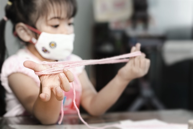 Little asian girl wearing facial hygienic mask playing cats cradle game at home,selective focus. quarantine,home isolation during covid-19 pandemic.