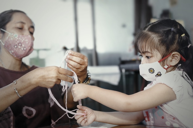 Little asian girl wearing facial hygienic mask playing cats cradle game with her mother at home, selective focus. quarantine,home isolation during covid-19 pandemic.