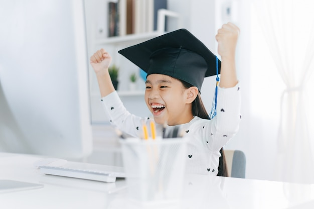 Little asian girl wearing graduate hat doing homework and smile with happiness for success of education.
