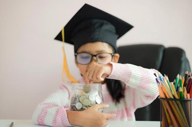 Little asian girl wearing graduate hat hugging clear glass jar