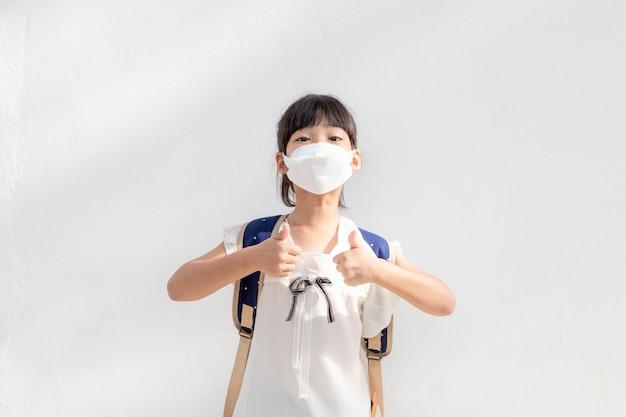 Pm2.5を保護するためのマスクを身に着けている小さなアジアの女の子と屋外の良い空気のための親指を立てるジェスチャーを表示します。大気汚染pm2.5とコロナウイルスの概念