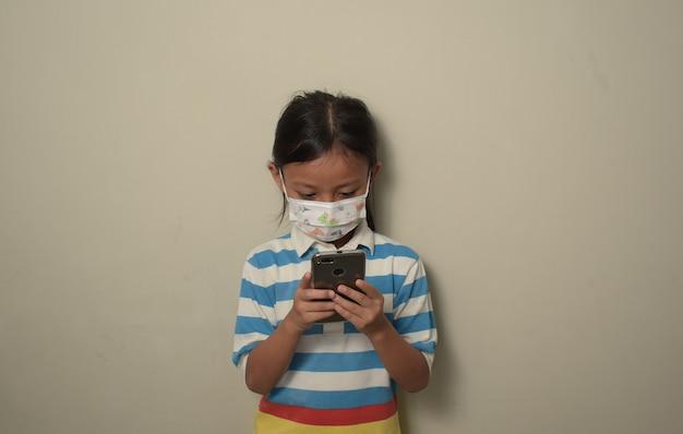 격리된 배경 위에 스마트폰을 사용하여 의료용 마스크를 쓴 아시아 소녀
