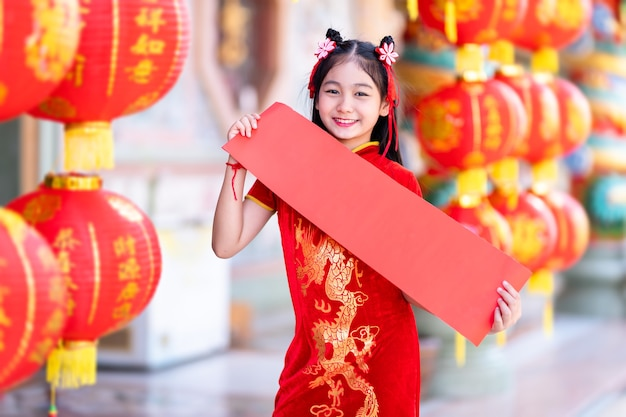 Маленькая азиатская девочка в красном традиционном китайском чонсаме, показывает красный чистый лист бумаги и фонари с китайским текстом «благословения», написанным на нем - это благословение удачи на китайский новый год