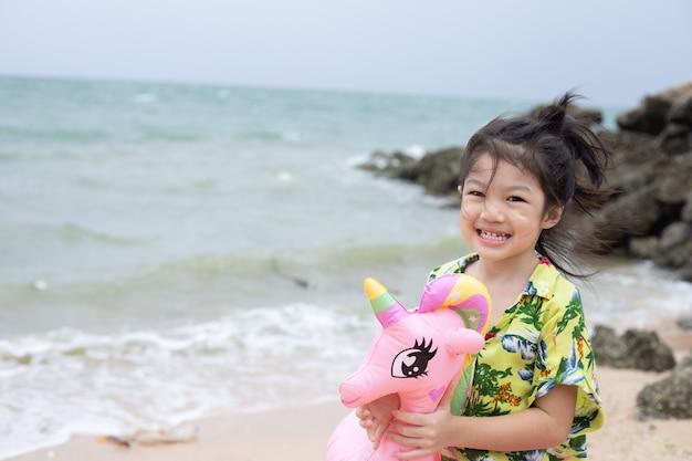 해변에서 수영 반지와 함께 작은 아시아 소녀.