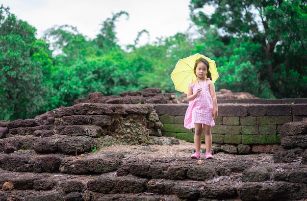 Little asian girl with yellow umbrella standind on th rock of historic site in thailand